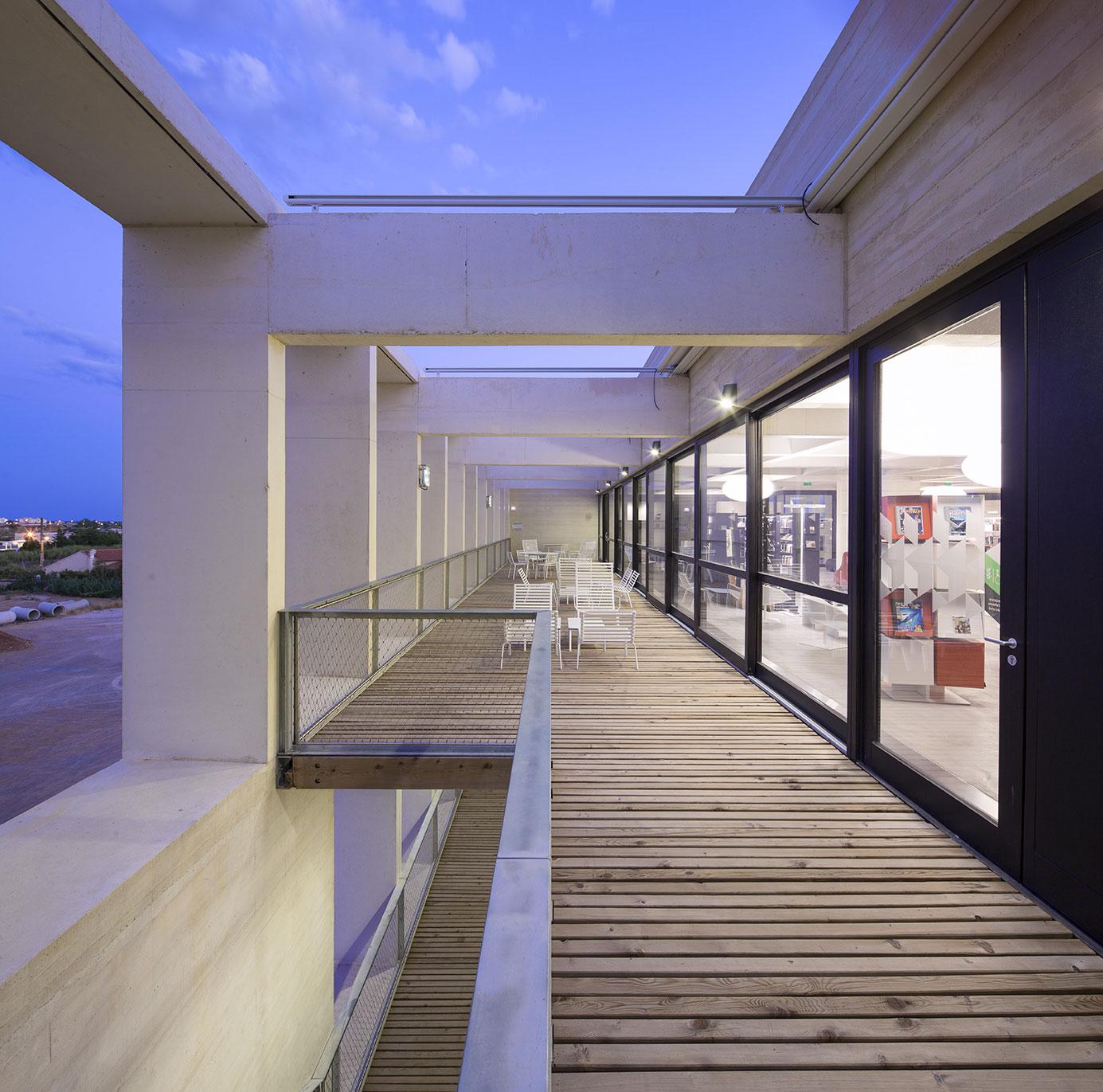 Tautem architecture - mediatheque Montaigne Frontignan - terrasse de lecture et arcades en béton - vue du soir